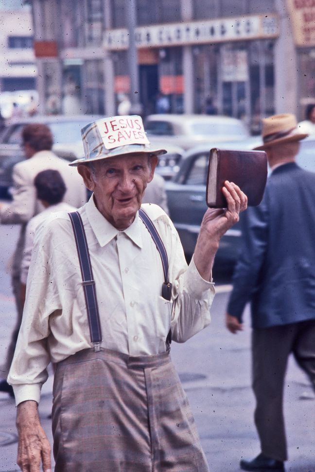 Man_holding_Bible_and_sporting_Jesus_Saves_sign_on_his_hat